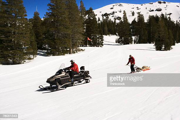 Ski patrol with injured person and snowmobile