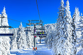 ski resort Kopaonik, Serbia, slope, people on the ski lift, skiers on the piste among white snow pine trees