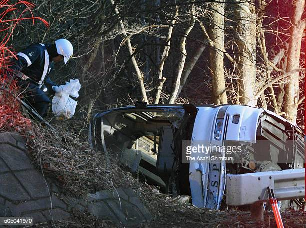 A ski tour bus lies on its side on the cliff off a road on January 15 2016 in Karuizawa Nagano Japan The ski bus carrying 41 people slid off a road...