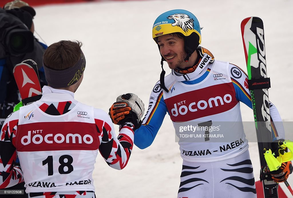 FIS Ski World Cup 2015/2016 men's slalom winner Felix Neureuter of Germany (R) congratulates third placed Marco Schwarz of Austria (L) at the finishing area at the Naeba ski resort in Yuzawa town, Niigata prefecture on February 14, 2016. AFP PHOTO / TOSHIFUMI KITAMURA / AFP / TOSHIFUMI KITAMURA