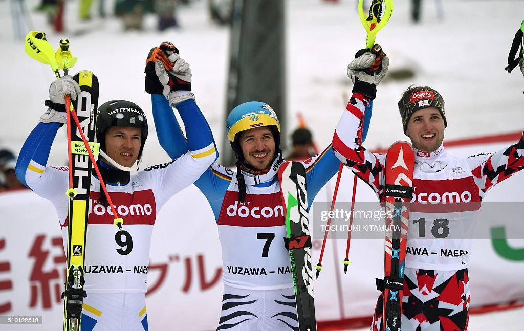 FIS Ski World Cup 2015/2016 men's slalom winner Felix Neureuter of Germany (C), second place Andre Myhrer of Sweden (L) and third place Marco Schwarz of Austria (R) raise their arms to acknowledge cheers at the finishing area at the Naeba ski resort in Yuzawa town, Niigata prefecture on February 14, 2016. AFP PHOTO / TOSHIFUMI KITAMURA / AFP / TOSHIFUMI KITAMURA