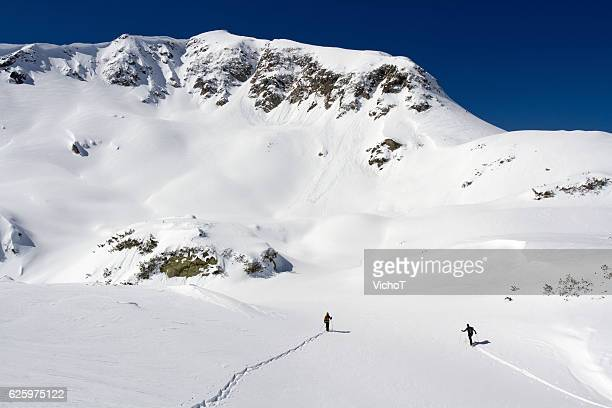 Skier and snowboarder heading up into winter mountain