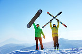 Skier and snowboarder stands mountain top with ski and snowboard in hands. Skiing and snowboarding concept. Sheregesh ski resort