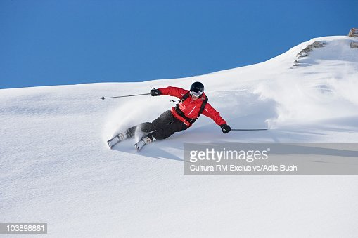 Skier carving turn through fresh powder : Stock Photo