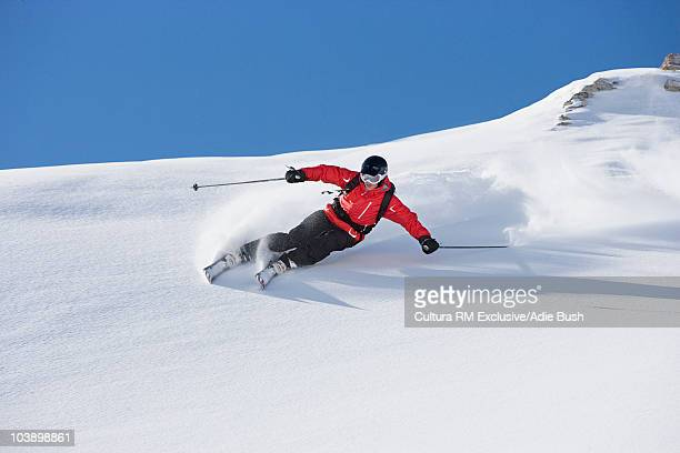 Skier carving turn through fresh powder