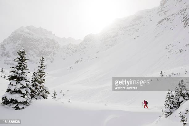 Skier climbs snowy ridge below misty mountains