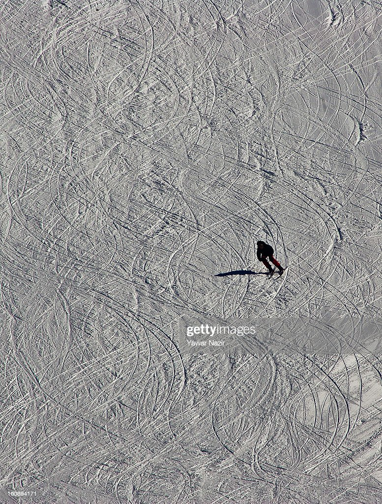 A skier descends on the slopes on February 07, 2013 in Gulmarg, 54 km (35 miles) to the west of Srinagar, the summer capital of Indian-administered Kashmir, India. Skiers from around the globe have descended on the ski resort of Gulmarg, known for long-run skiing, snow-boarding, heli-skiing and steep mountains. Located less than six miles from the ceasefire line or Line of Control (LoC) that divides Kashmir between India and Pakistan. Tourists have begun to return to Kashmir as various foreign governments have relaxed their travel advisory warnings to citizens travelling in the previously strife-torn region.