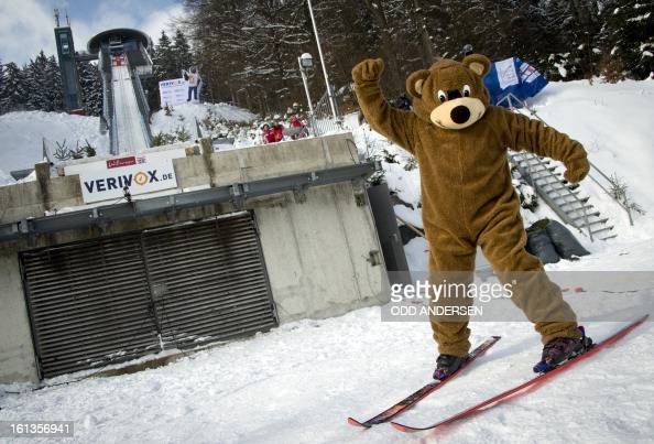 A skier dressed in a bear costume gets ready to ski down the lower part of the jump as the start of the FIS Ski Jumping World Cup individual large...