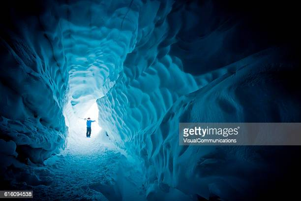 Skier exploring ice cave.