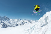 A skier in full sports equipment jumps into the precipice from the top of the glacier against the background of the blue sky and the Caucasian snow-capped mountains. Elbrus region. Russia.
