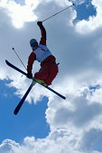 Skier in mid-air jump, grabbing one ski, low angle view