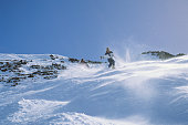 Skier in powder down moguls, Squaw Valley, California, USA