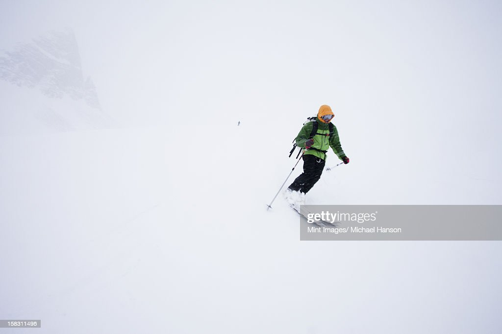 A skier in powder snow in mist and cloud conditions on the Wapta Traverse, a mountain hut to hut ski tour in Alberta, Canada.