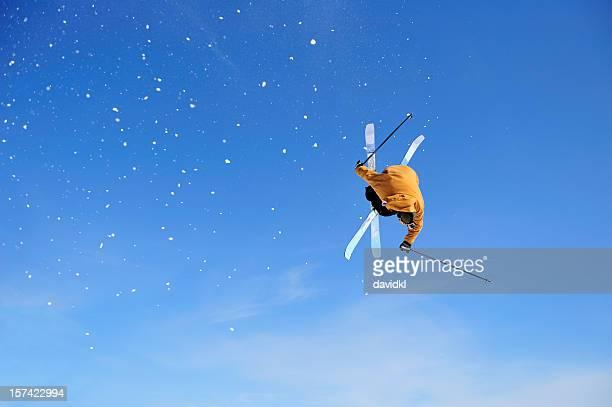 Skier Iron Cross stunt against blue sky