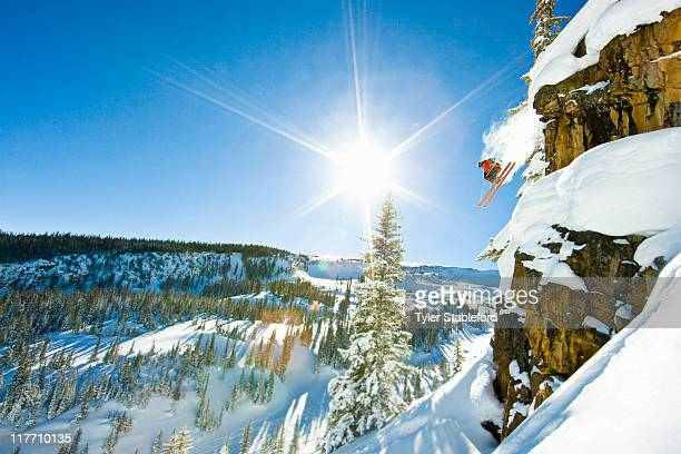 Skier jumping cliff on sunny winter day.