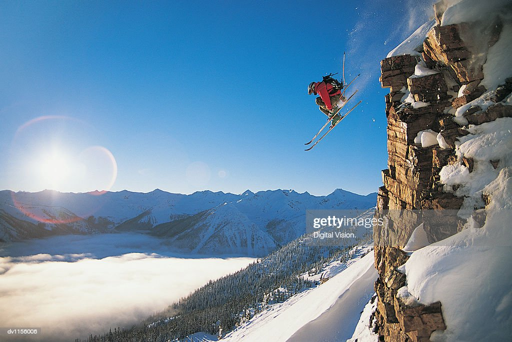 Skier Jumping Mid Air off a Steep Rock Face off Piste