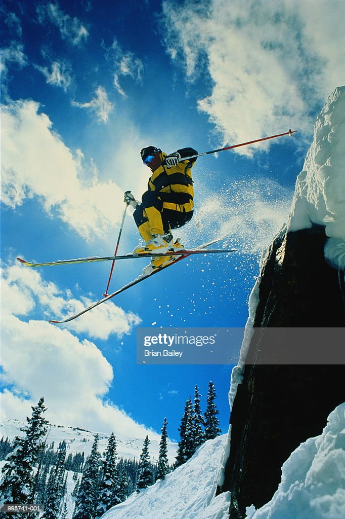 Skier jumping off cliff, blue sky with clouds in background