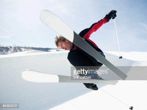 Skier jumping off lip of half-pipe