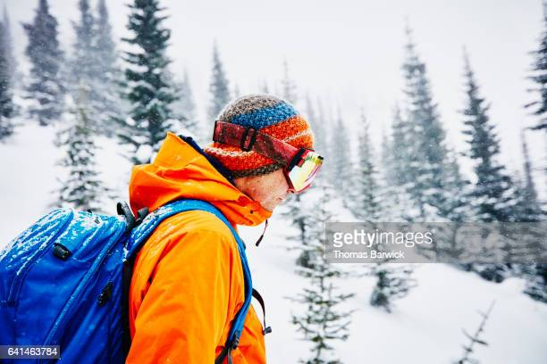 Skier looking at line before descending during backcountry ski tour