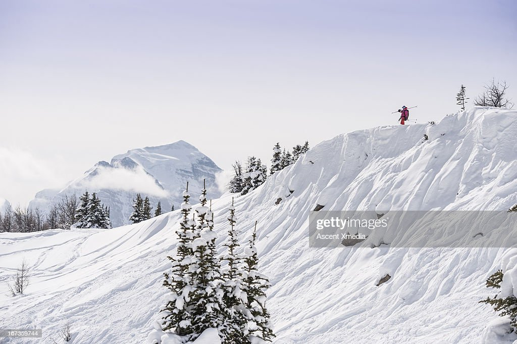 Skier looks off from top of off-piste run, mtns : Stock Photo