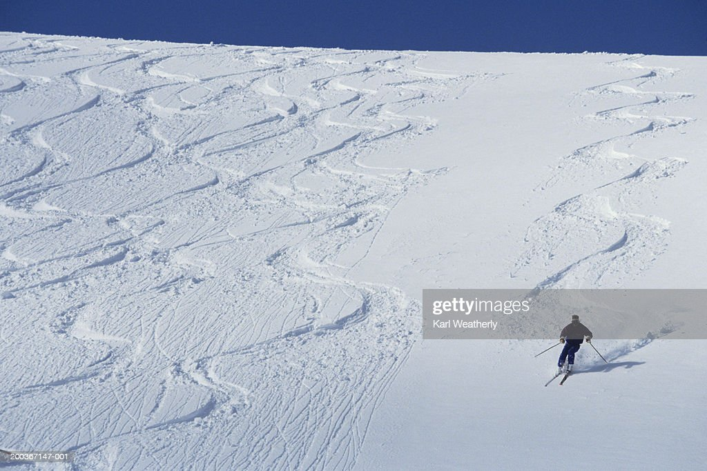 Skier making tracks, other tracks visible, elevated view