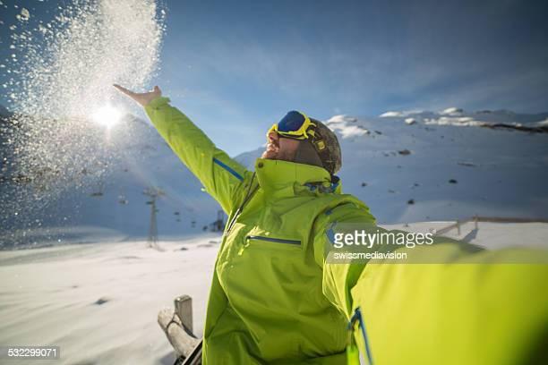 Skier man taking selfie on ski slopes throwing snow-Sunset time