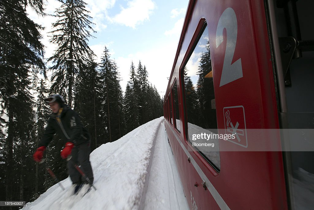 A skier passes a SBB AG train on the side of the railway track as it heads towards the town of Davos, the venue of the World Economic Forum's (WEF) 2012 annual meeting, in Davos, Switzerland, on Sunday, Jan. 22, 2012. German Chancellor Angela Merkel will open next week's World Economic Forum in Davos, Switzerland, which will be attended by policy makers and business leaders including U.S. Treasury Secretary Timothy F. Geithner. Photographer: Chris Ratcliffe/Bloomberg via Getty Images