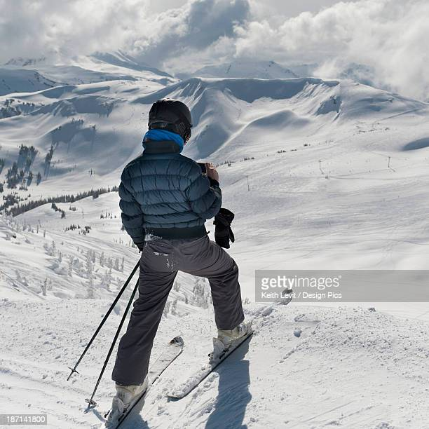 A Skier Pauses On The Trail To Look Out Over The Mountains
