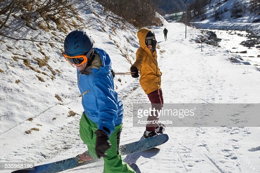 Skier pulls snowboarder along path in mountains : Stock Photo