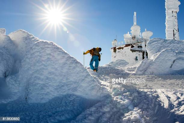 Skier reaching mountain peak in a cold and sunny weather