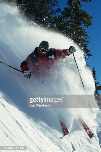 Skier riding down slopes with snow spray