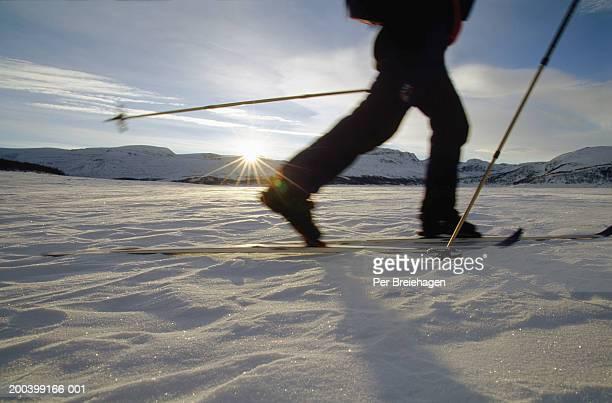 Skier skiing across lake at sunset