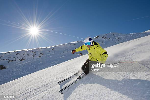 Skier skiing down a mountain in front of the sun