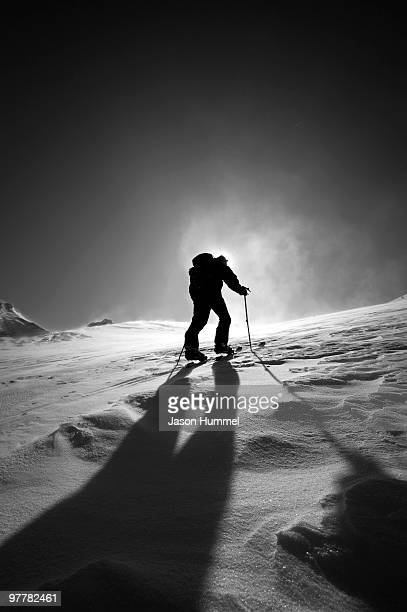 A skier skinning up Mount Baker, Washington with the sun behind him and a shadow cutting across the