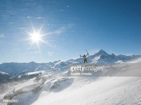 Skier stands on summit as wind blows snow,arms out : Stock Photo
