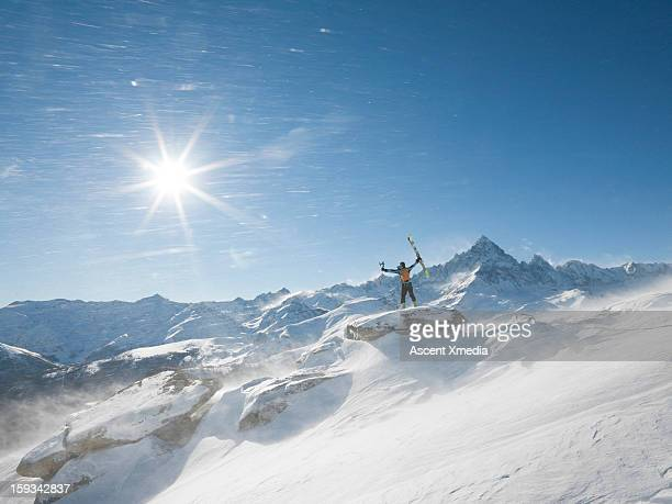 Skier stands on summit as wind blows snow,arms out