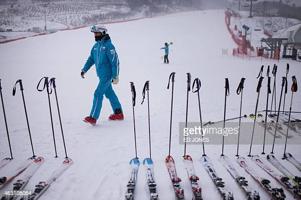 A skier walks past skis at the bottom of a slope at the Alpensia resort a venue of the Pyeongchang 2018 winter Olympics in Pyeongchang on February 10...