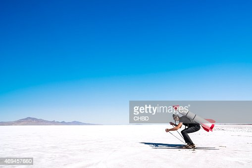 Skier with a rocket on his back on the desert.