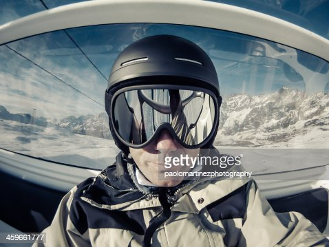 Skier with ski goggles and helmet on the chairlift