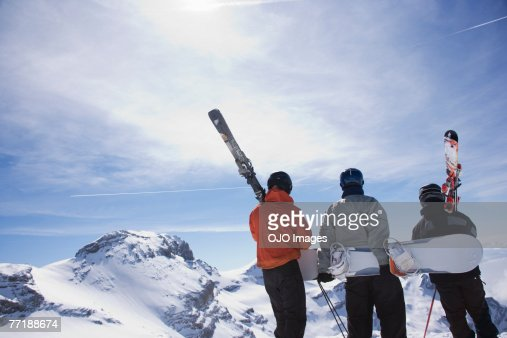Skiers and a snowboarder on a mountain carrying their equipment : Stock Photo