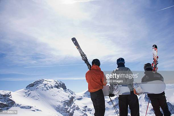 Skiers and a snowboarder on a mountain carrying their equipment