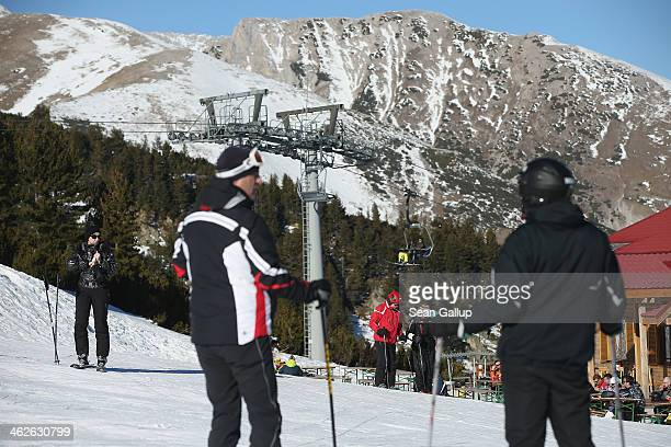 Skiers and snowbaorders prepare to descend a slope at the Bansko ski resort on January 13 2014 in Bansko Bulgaria Located in the Pirin mountains in...