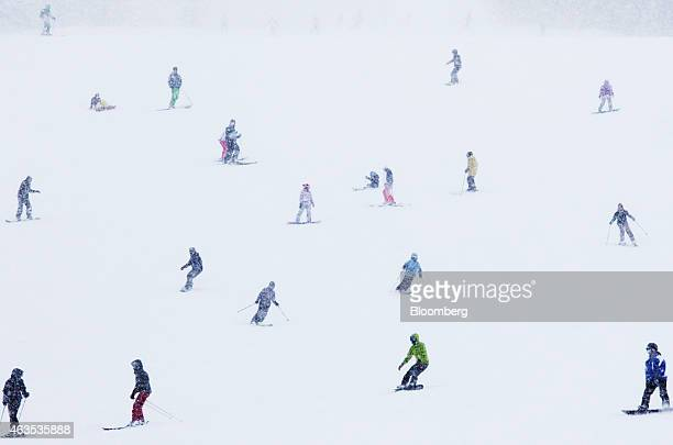 Skiers and snowboarders ride down a slope at the Niseko Hanazono resort operated by Nihon Harmony Resorts KK in Kutchan Hokkaido Japan on Sunday Feb...