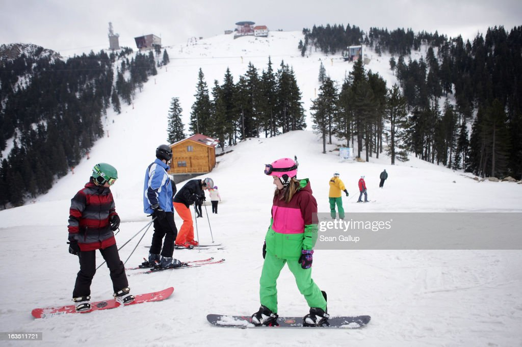 Skiers and snowboarders take in late winter pistes in the Bucegi mountains on March 9, 2013 at Poiana Brasov, Romania. Romania is eager to promote its approximately 20 ski resorts, of which Poiana Brasov is among the biggest, to foreign tourists. Both Romania and Bulgaria have been members of the European Union since 2007 and restrictions on their citizens' right to work within the EU are scheduled to end by the end of this year. However Germany's interior minister announced recently that he would veto the two countries' entry into the Schengen Agreement, which would not affect labour rights but would prevent passport-free travel.