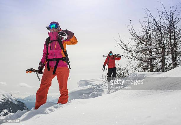 Skiers carry their skis towards start of off-piste