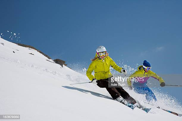 Skiers coasting on snowy slope
