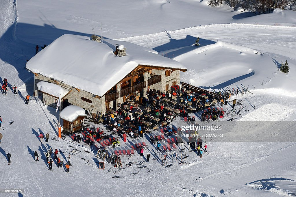 Skiers enjoy a restaurant on December 28, 2012, in the French Alps resort of Val-d'Isere. France's ski slopes are set to be busier than last year as early snow falls encourage higher bookings than last year, according to an industry spokesmen and a study released on December 18, 2012. AFP PHOTO/PHILIPPE DESMAZES