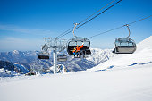Skiers, boy and father sitting on the chair on ski resort in Sochi, Russia