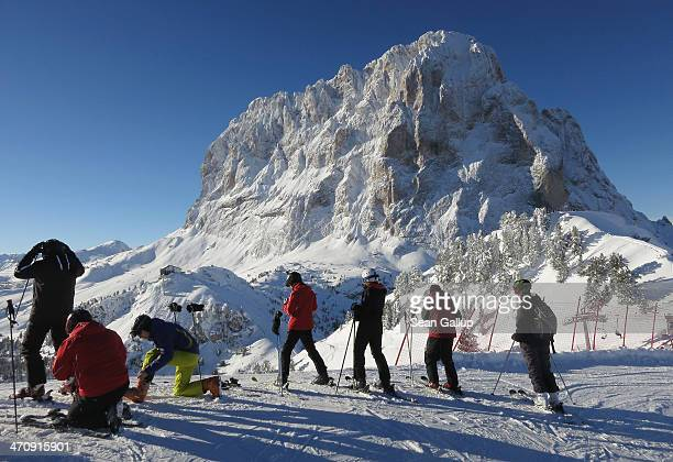 Skiers prepare to descend a slope at Val Gardena as Sassolungo mountain looms behind in the Dolomite SuperSki region on February 6 2014 near Santa...