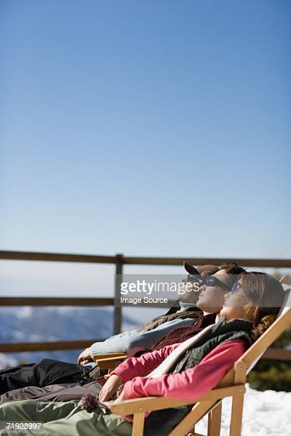 Skiers relaxing on deckchairs